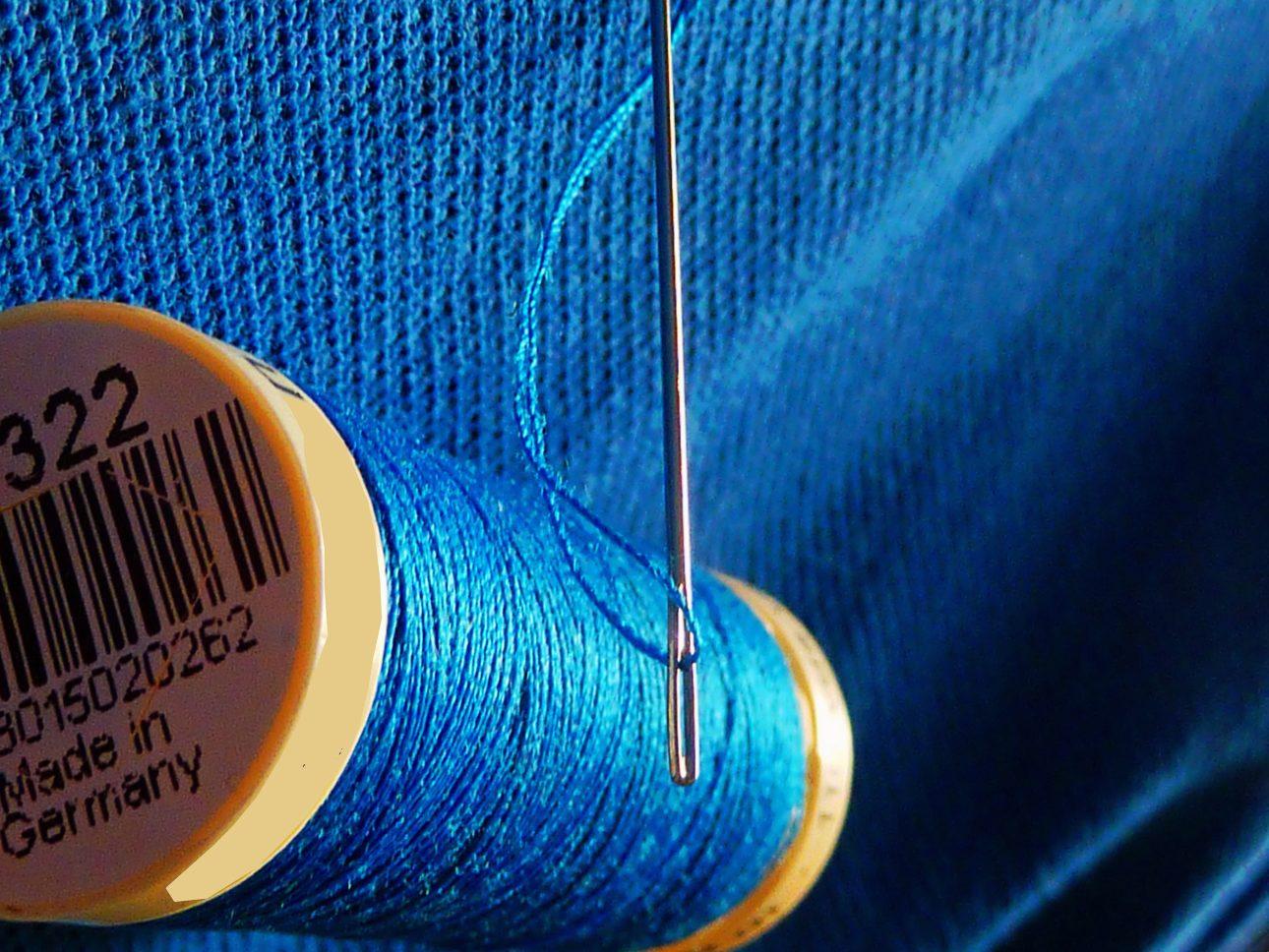 Rocchetto di filo azzurro e ago da cucire